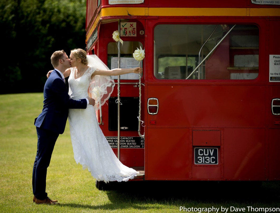 Bride and groom and a big red bus