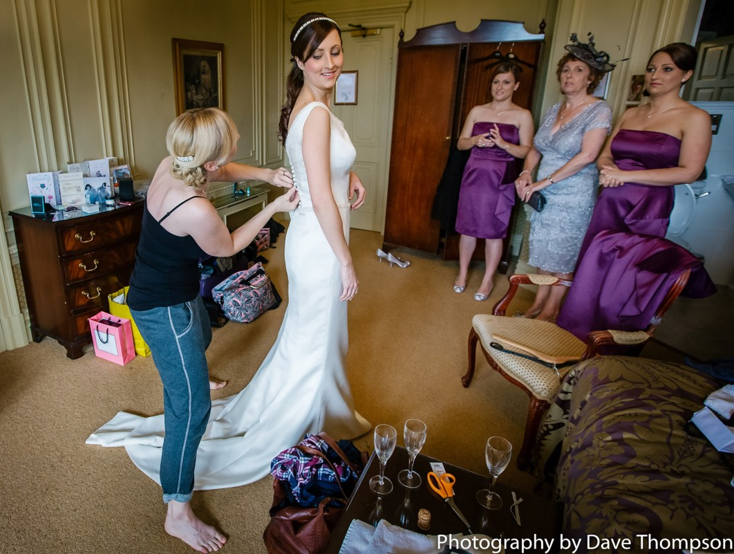 One of the bridesmaids helps the bride get into her dress