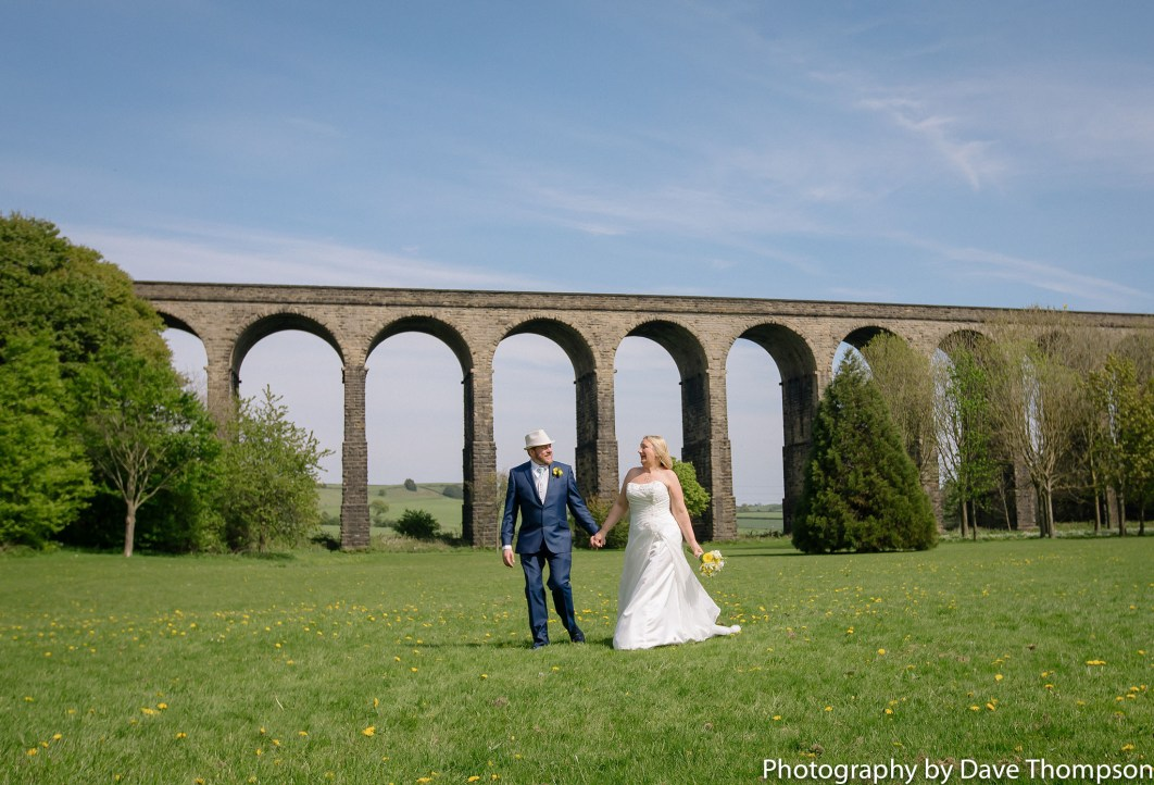 Bride and groom in front of a viaduct in Penistone