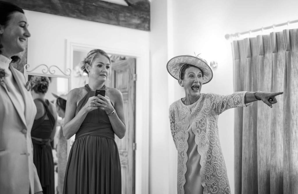 Mother of the bride laughs during the bridal preparations Photography by Dave Thompson