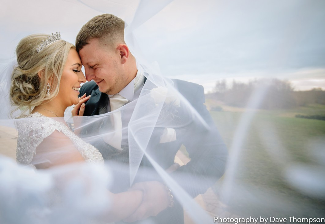 Bride and groom wrapped in a veil