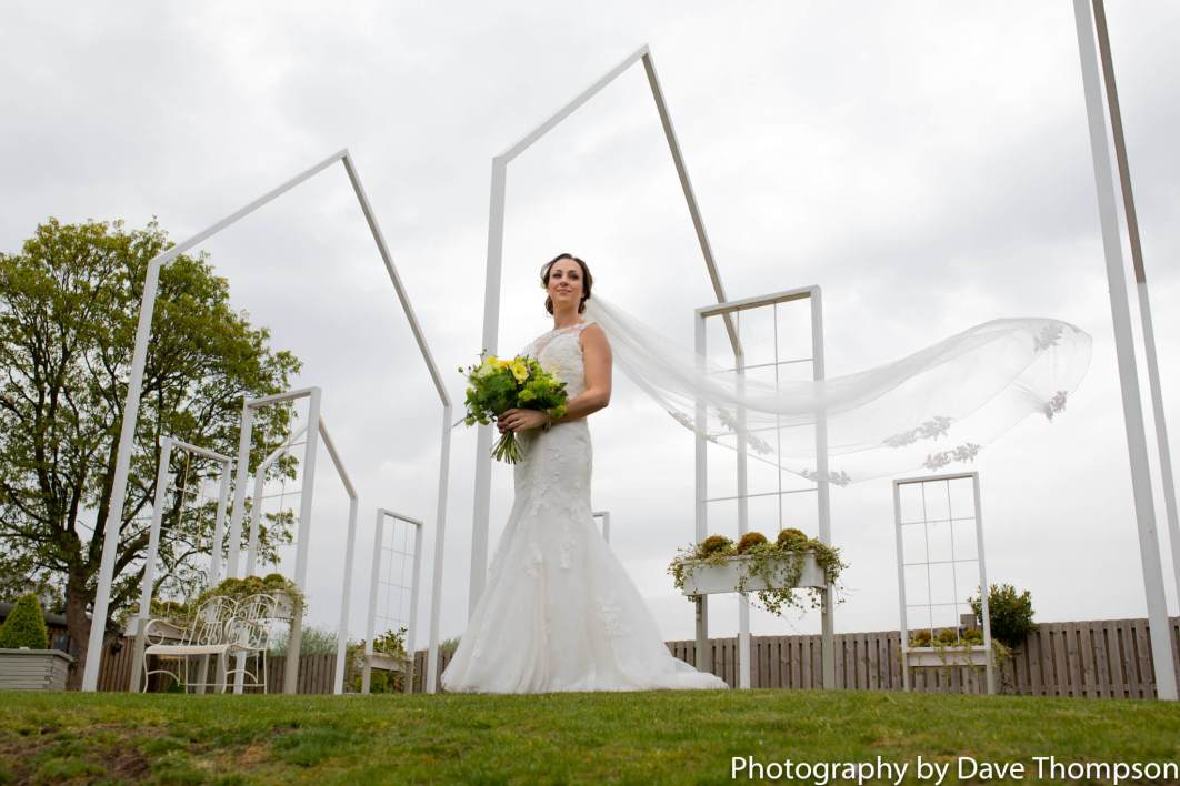 A brides veil blows in the wind next to the White House