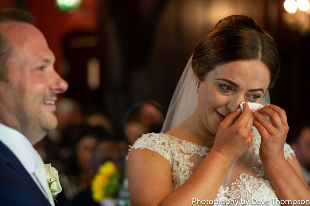 The bride wipes a tear form her eye