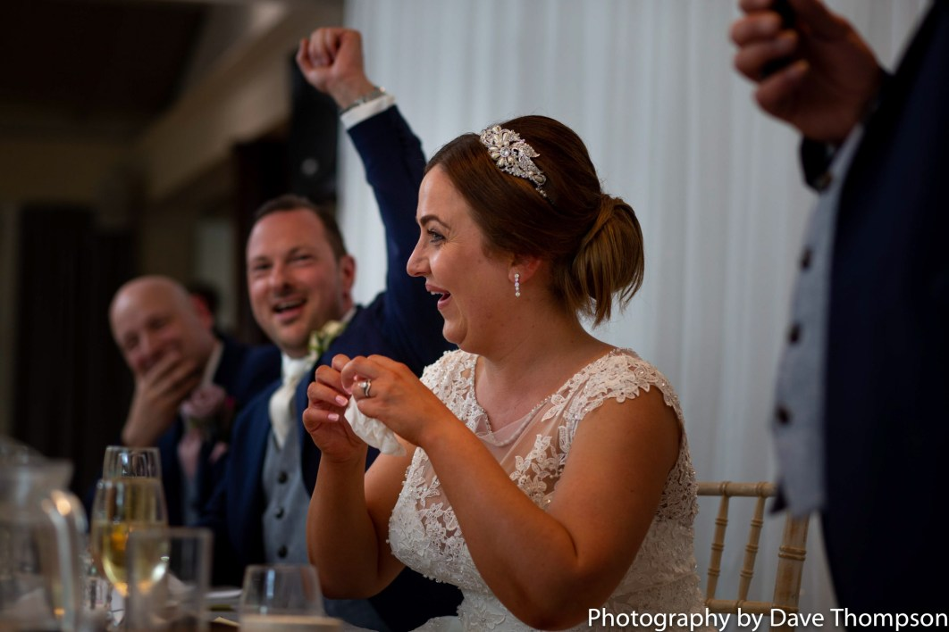 The bride and groom react during speeches