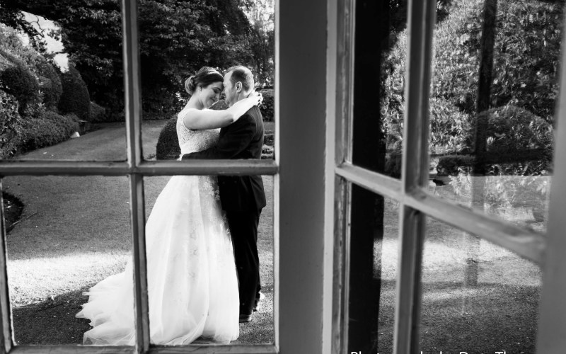 Bride and groom seen through a window