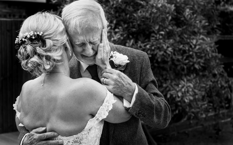The father of the bride cries as he sees his daughter for the first time in her wedding dress.