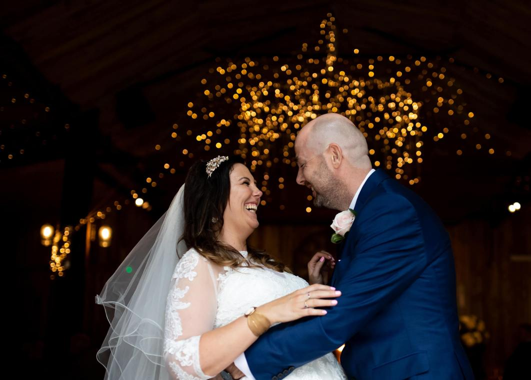The bride and groom laugh beneath fairy lights in the barn