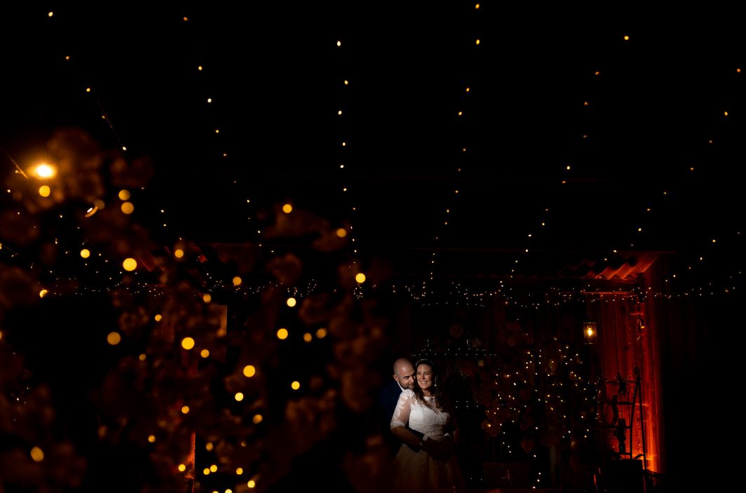 An off camera flash picture using fairy lights of the birde and groom