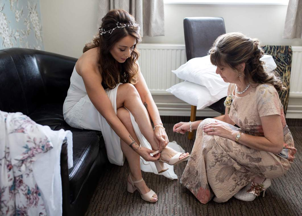 The bride is helped with her shoes by her mother