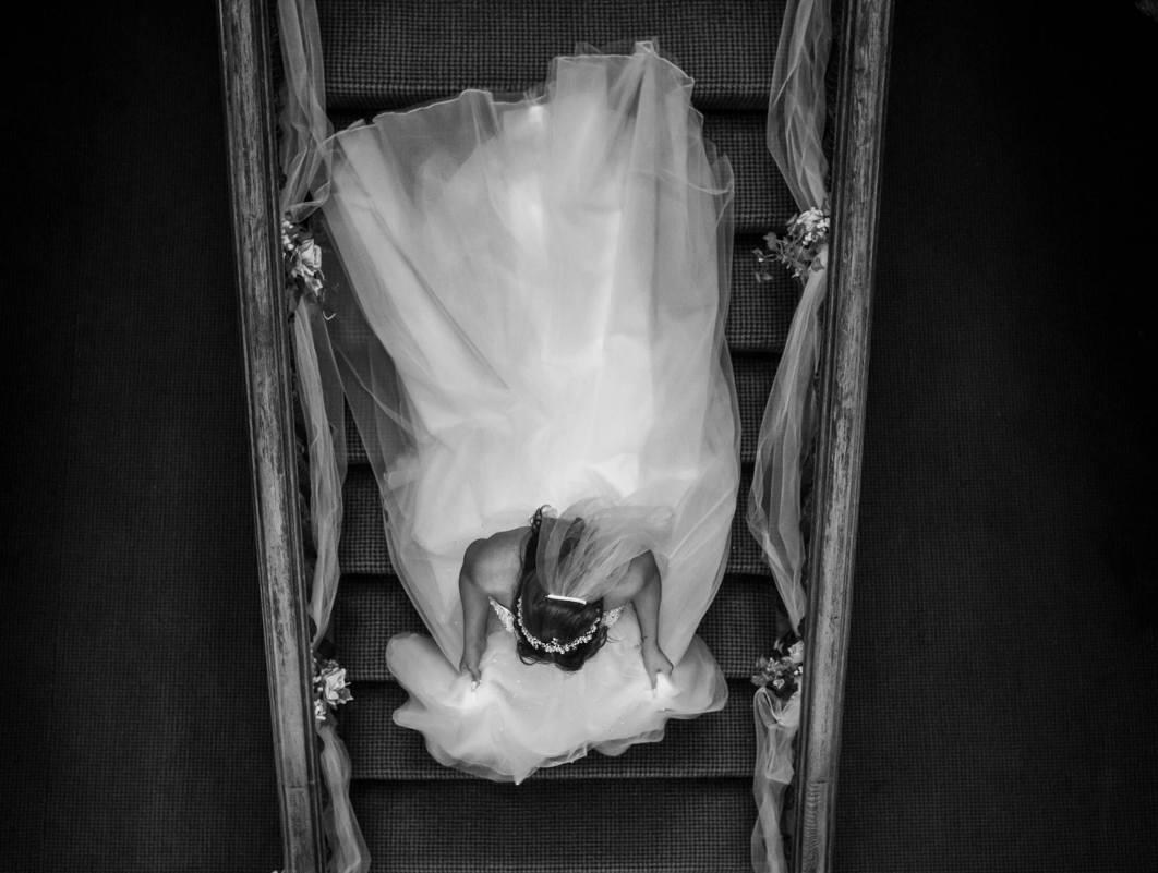 The bride walks down the stairs at Hollin Hall Hotel in Cheshire