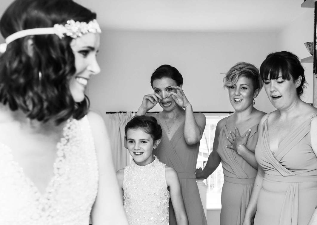 A group of bridesmaids react as a bride shows them her dress.