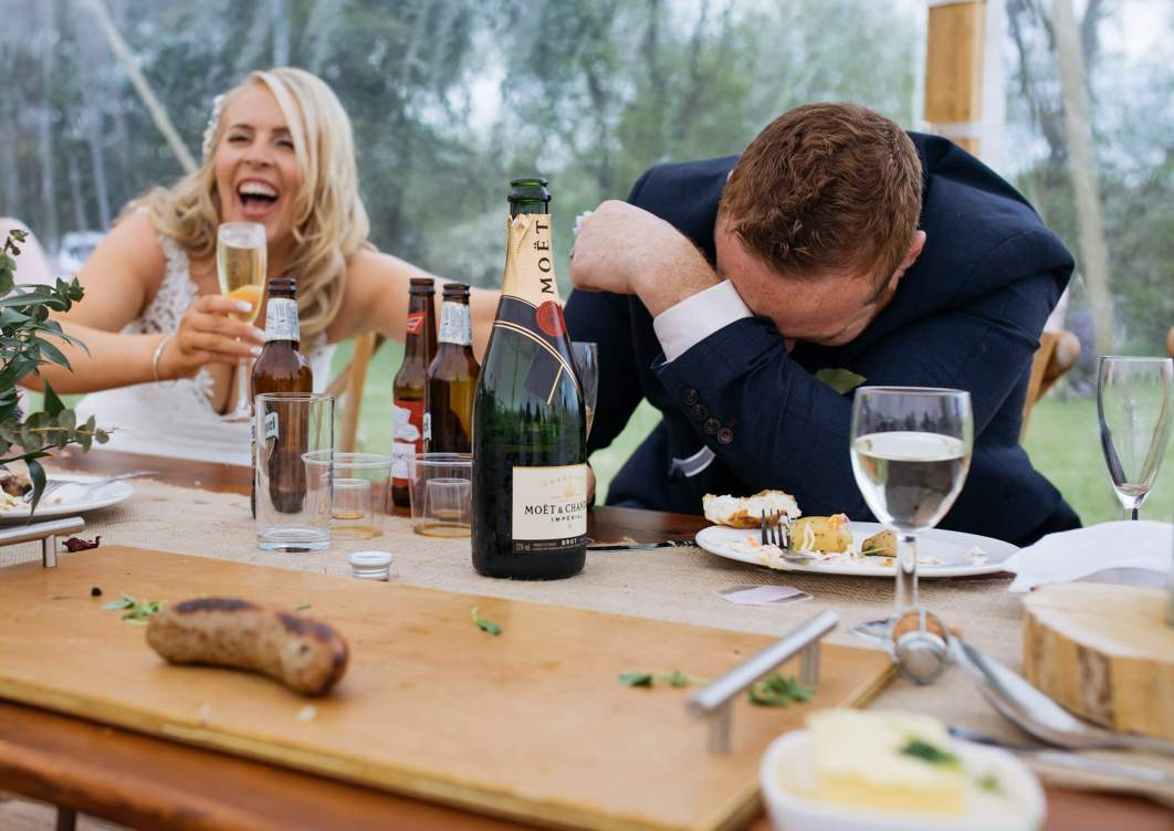 A groom slumps on a table as the bride laughs during the speeches