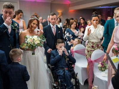 The bride is led down the aisle by her son in his wheelchair.
