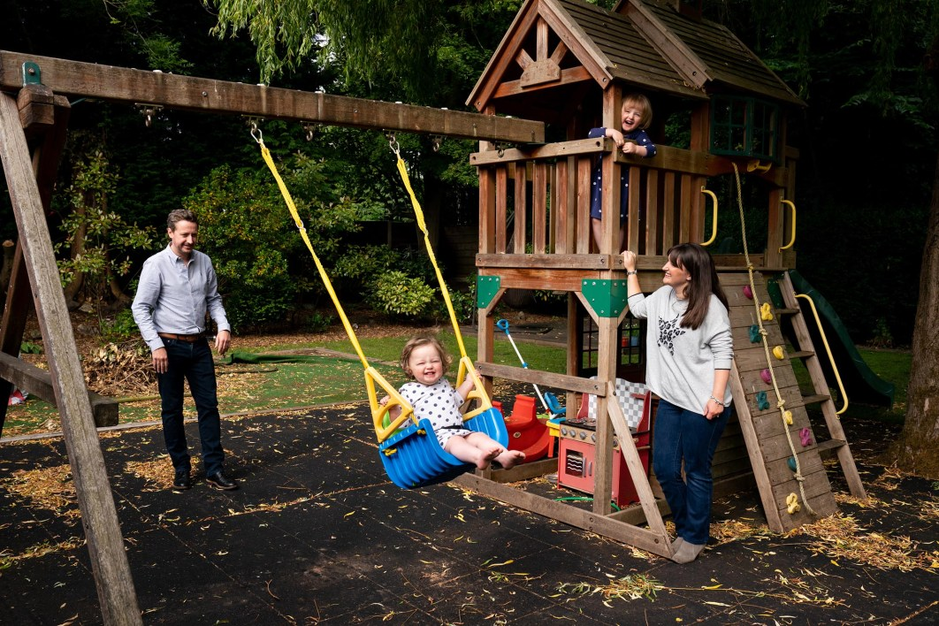 A family play on the swings in their garden