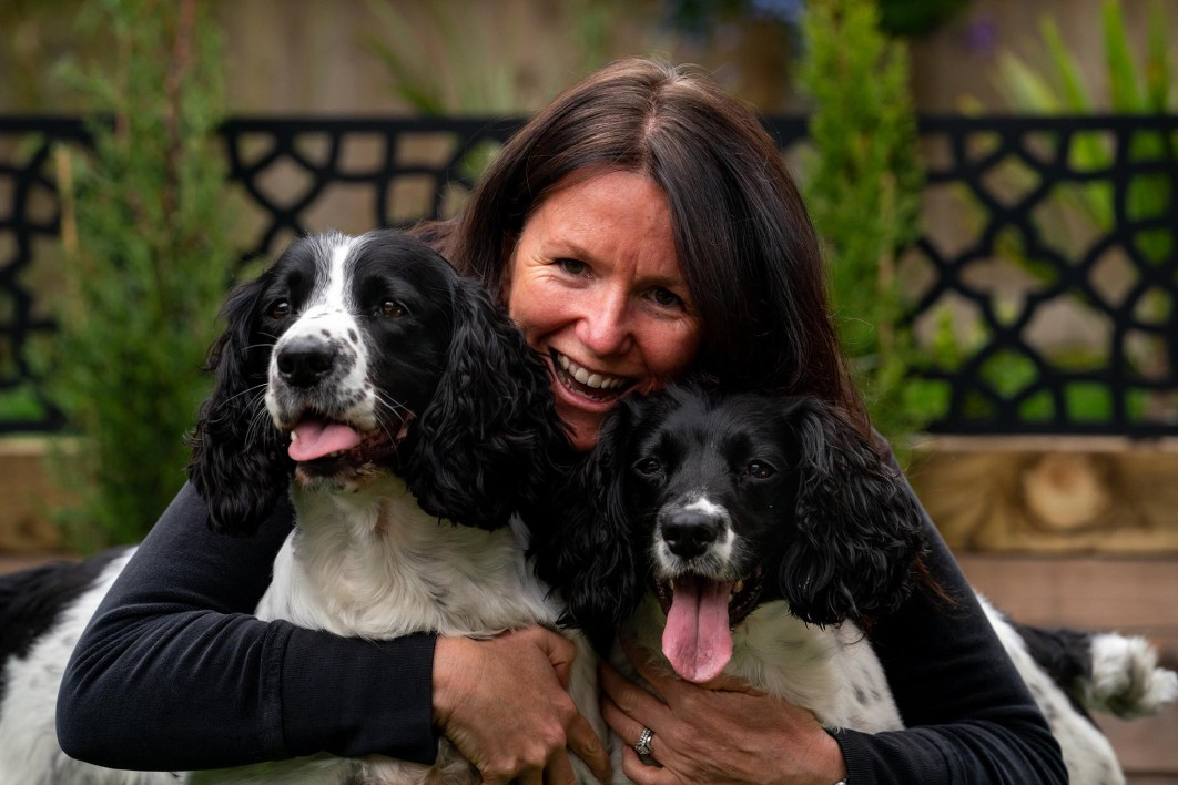 A woman poses with her dogs during a family photoshoot.