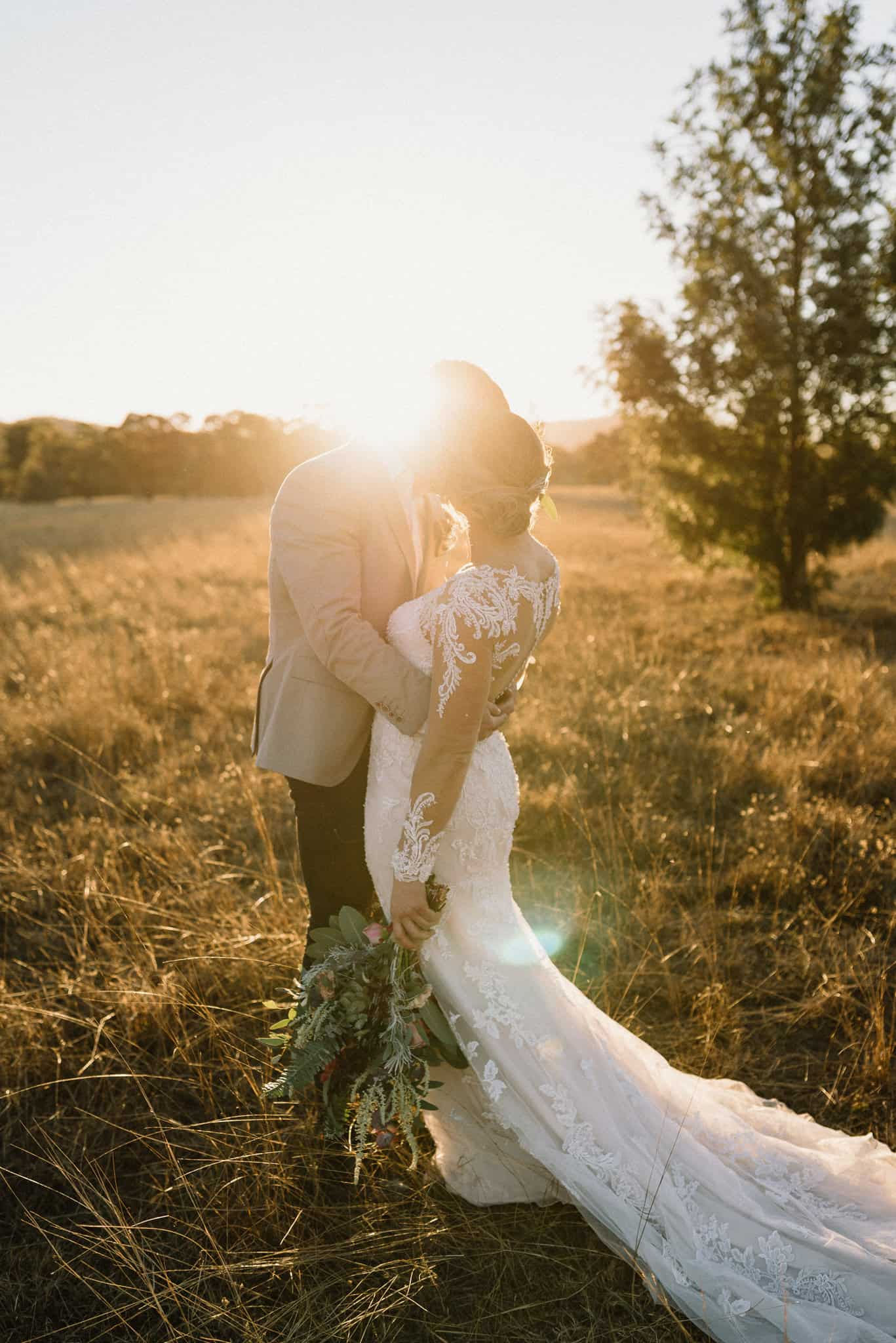 golden sun pours over bride and groom who stand in long grass field kissing
