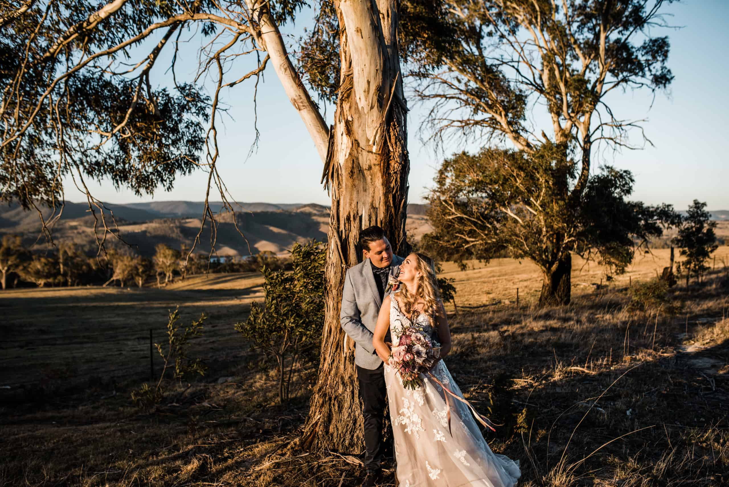 Bride and groom standing under a gumtree in Australia right after elopement ceremony.