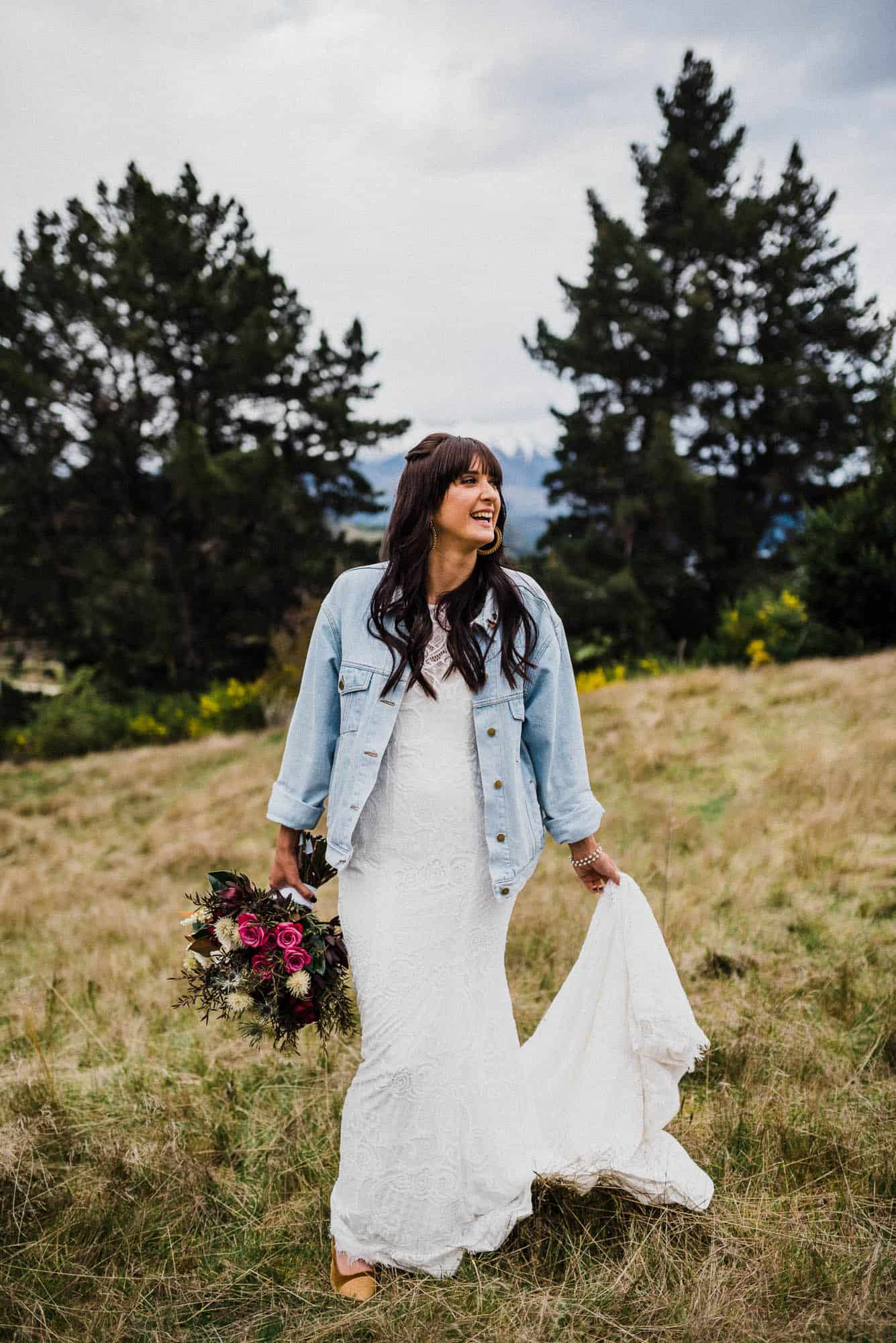 Bride poses for portrait on top of grassy hill with mountains and pine trees behind her on overcast day