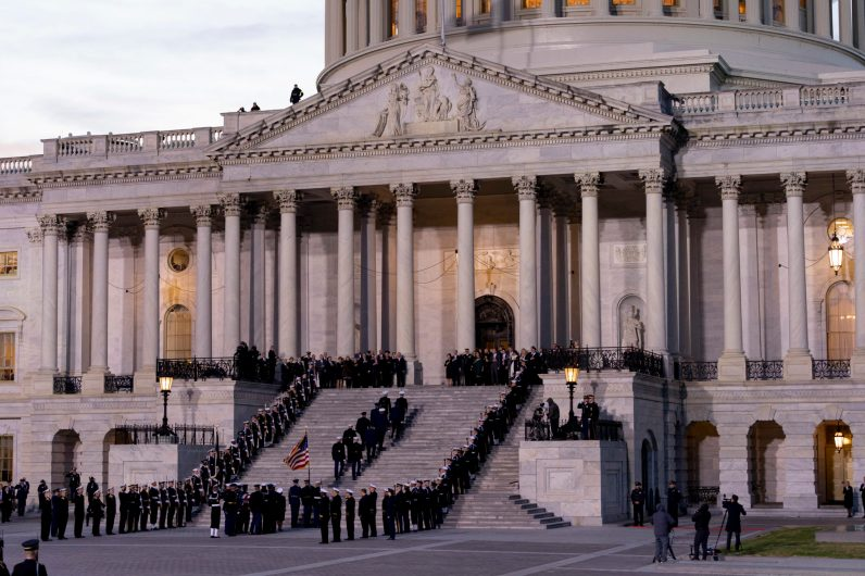 Former cabinet members from the administration of GEORGE HERBERT WALKER BUSH, the 43rd President of the United States, stand at the top of the Capitol steps to the left, and the his family member stand to the right, awaiting his body to be brought into the Capitol Rotunda to lie in State, December 3, 2018.