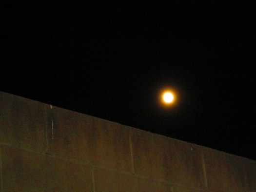 Moon Rising Above A Brick Wall