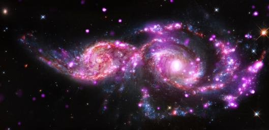 This composite image of NGC 2207 and IC 2163 contains Chandra data in pink, optical-light data from NASA's Hubble Space Telescope in red, green, and blue (appearing as blue, white, orange, and brown), and infrared data from Spitzer Space Telescope in red.