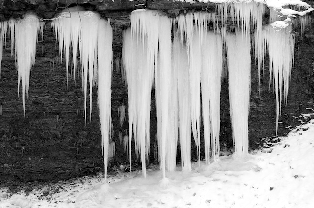 shale cliff of icicles in black and white