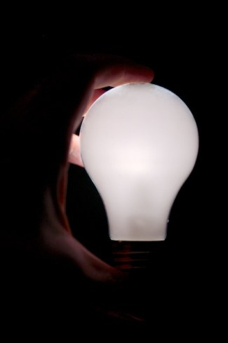 Light Bulb, lit, in a hand