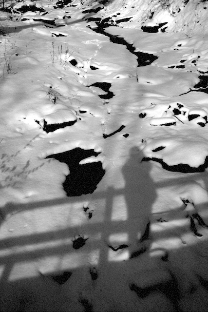 Snow bound creek with a shadow of the photographer on a bridge