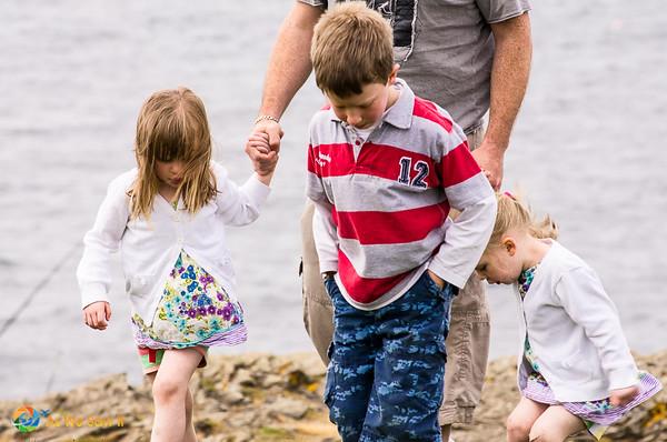 Father holding children's hands at Loop Head cliffs, near Kilkee, Ireland