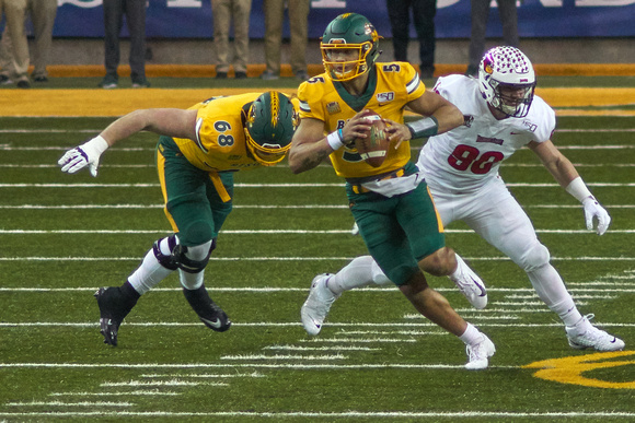 NDSU QB #5 Trey Lance runs 9 yards and gains the First Down. Hes tackled by LB #42 Dylan Draka. Its Third and 8 at the ISU 43, 10:30 First Quarter -<small>Photo 072 by Craig Maas</small>