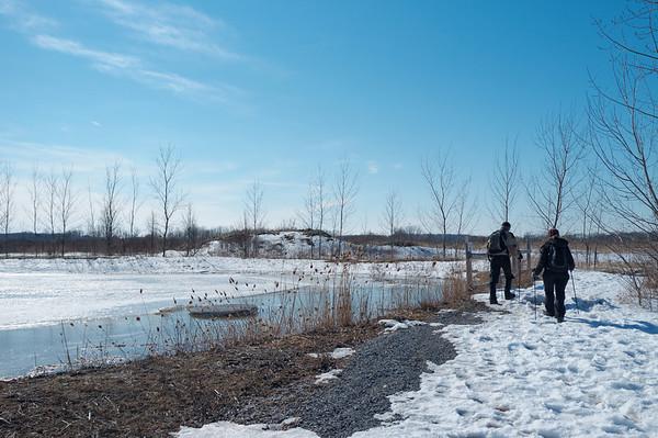 Trekking past a nice partially frozen pond or reservoir
