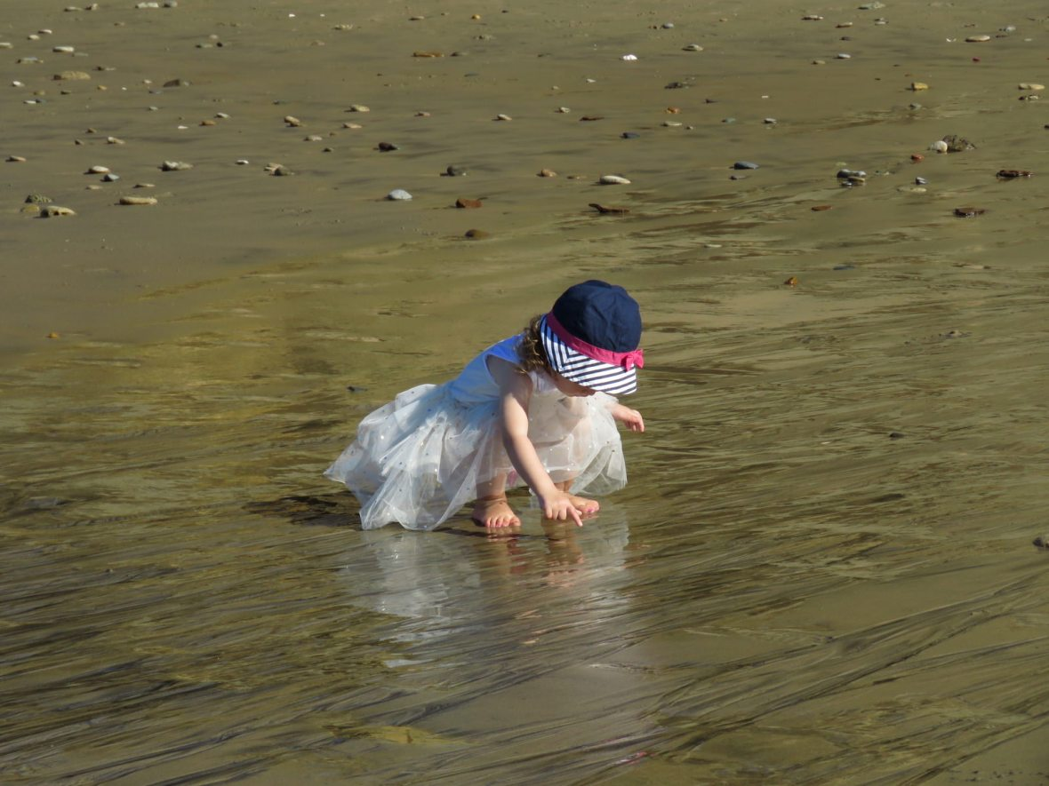toddler squatting in wet sand on the beach