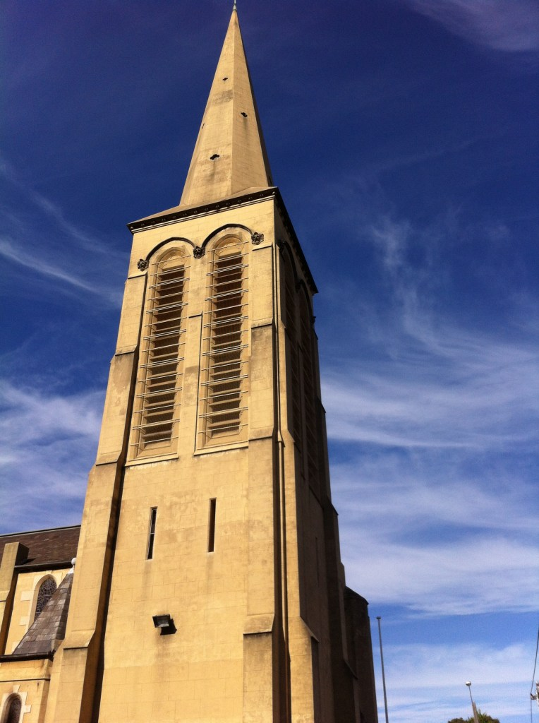 sandstone church steeple against blue sky and wispy clouds