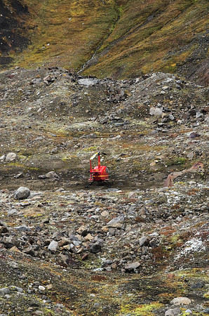 The Robinson R44 parked on a flat spot on a mountain in the Alaska Range.