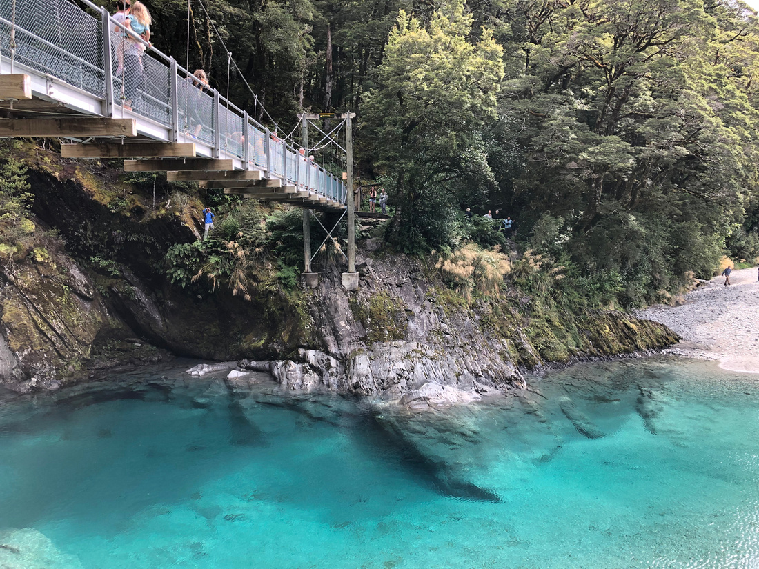 Turquoise blue pools sit beneath a bridge while tourists meander along the banks of the river and under the bridge footings.