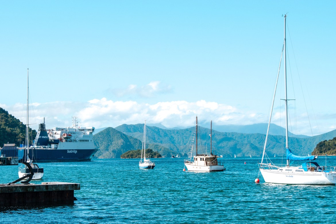 New Zealand Cities: Picton New Zealand. A view of the harbor at Picton, New Zealand. The Interislander ferry sits beyond smaller fishing vessels and sail boats floating in the harbor.  Native bush covers the hillsides surrounding the harbour leading to Cook Strait and the North Island.