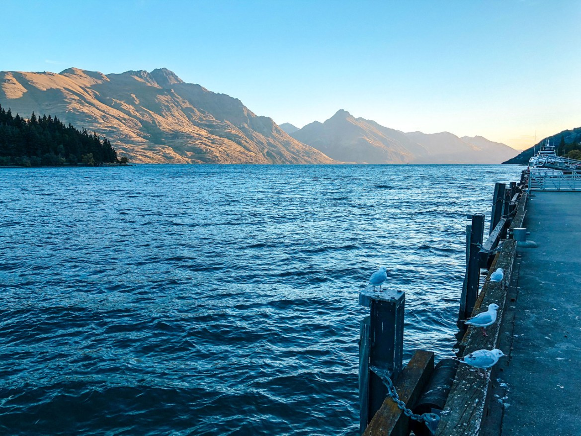 A view of Lake Wakatipu from the pier downtown Queenstown at sunset.  Bayonet Peaks and Walter Peak are both visible over the lake.