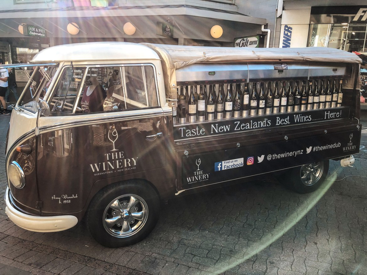 A fully restored Volkswagen Bus from The Winery displays dozens of local New Zealand wines for sale in Queenstown.