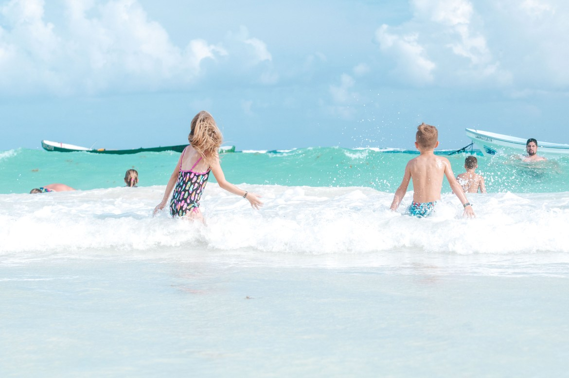 Young children play in the turquoise blue water of the Caribbean Sea at Playa Paraíso, near Tulum, Quintana Roo, Mexico, on the Yucatan Peninsula.  An anchored fishing boat floats further out in the surf, and other swimmers enjoy the warm waters at the best beach in Tulum.