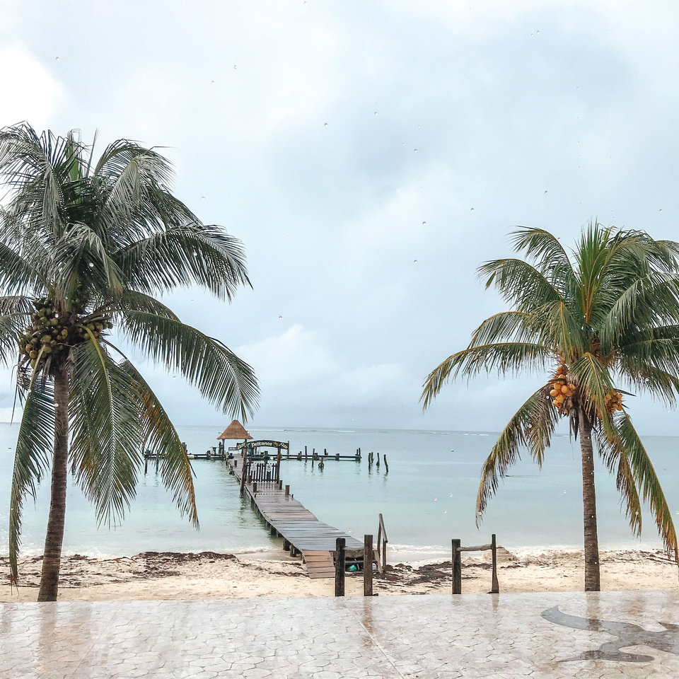 The view of white sand beaches and a pier looking out from a restaurant in Mexico's Puerto Morelos, a town South of Cancún along the Riviera Maya.  A pier extends out into the Caribbean Sea, and palm trees heavy with coconuts border the water.