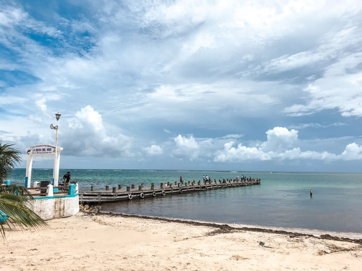 Things to do in Puerto Morelos Mexico. Mexico's Puerto Morelos, South of Cancún along the Riviera Maya.  The sun shines over the turquoise-blue waters of the Caribbean Sea and a pier juts out into the water.  Blue sky peeks through billowing white and grey clouds along the horizon.