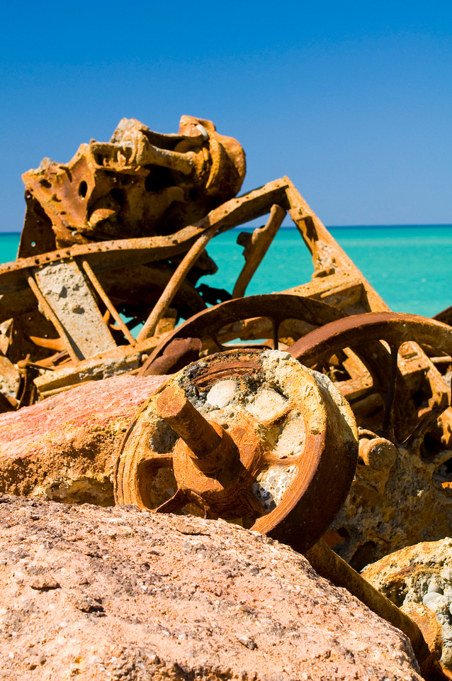 Image Bank: Coastal Landscapes.  Rusted metal ore carts and other old machinery sit at the edge of the beach and the Pacific Ocean near Timaru, New Zealand, on the South Island.  The turquoise blue ocean and blue sky contrast with the rust-colored metal in the foreground.
