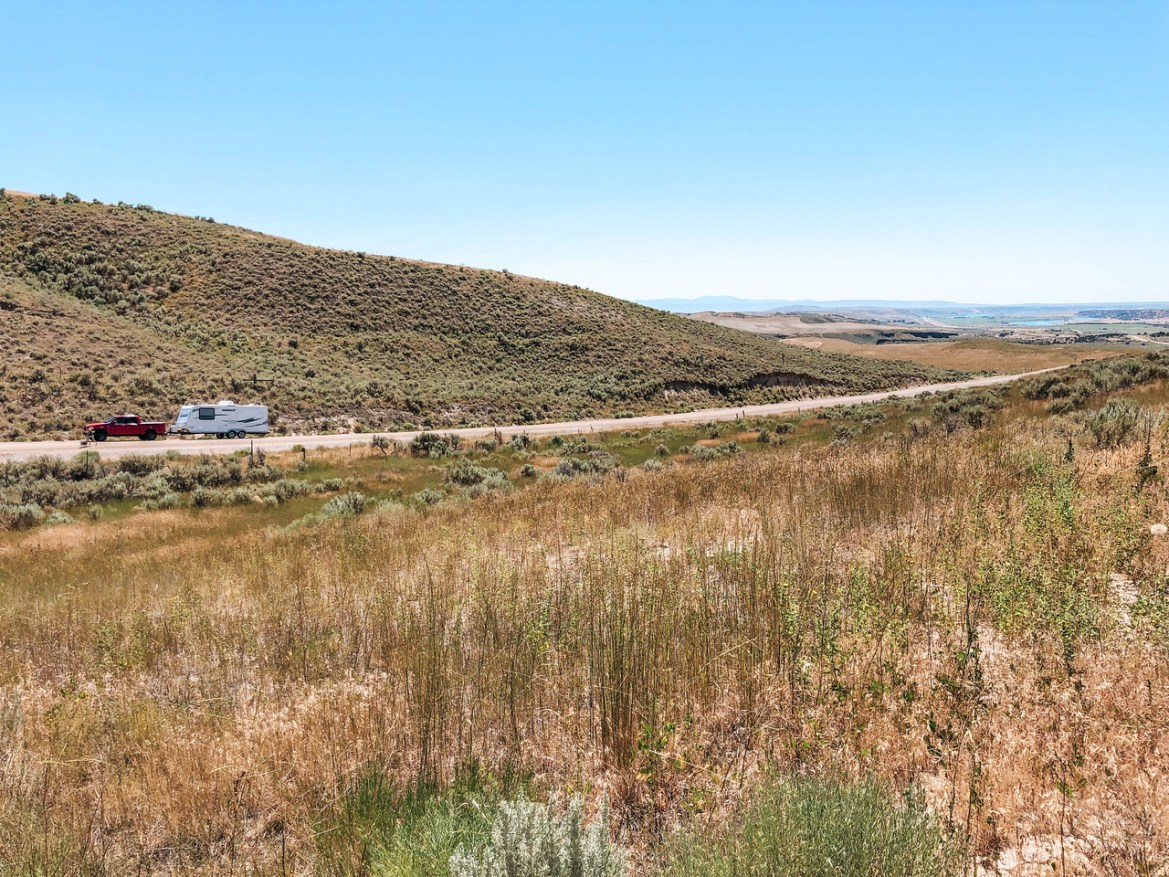 Day 1 of our recommended Yellowstone Vacation Itinerary: Yellowstone Road Trip.  Our Ford F-150 Lariat sits with our Starcraft travel trailer on a rural dirt road near Massacre Rocks State Park and American Falls, Idaho.  Brown foliage surrounds Deeg Road in Eastern Idaho's high desert.