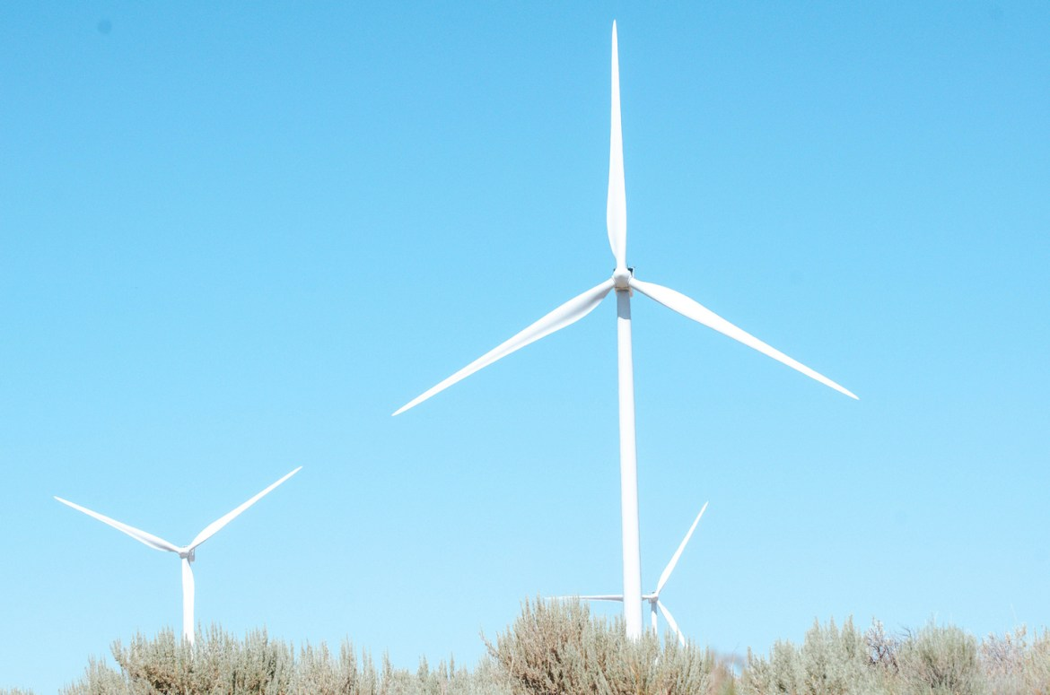 Giant wind turbines sit in rural farmland near Massacre Rocks State Park and American Falls, Idaho.  Blue skies contrast with the long, white arms of the turbines as they spin in the wind in Eastern Idaho.