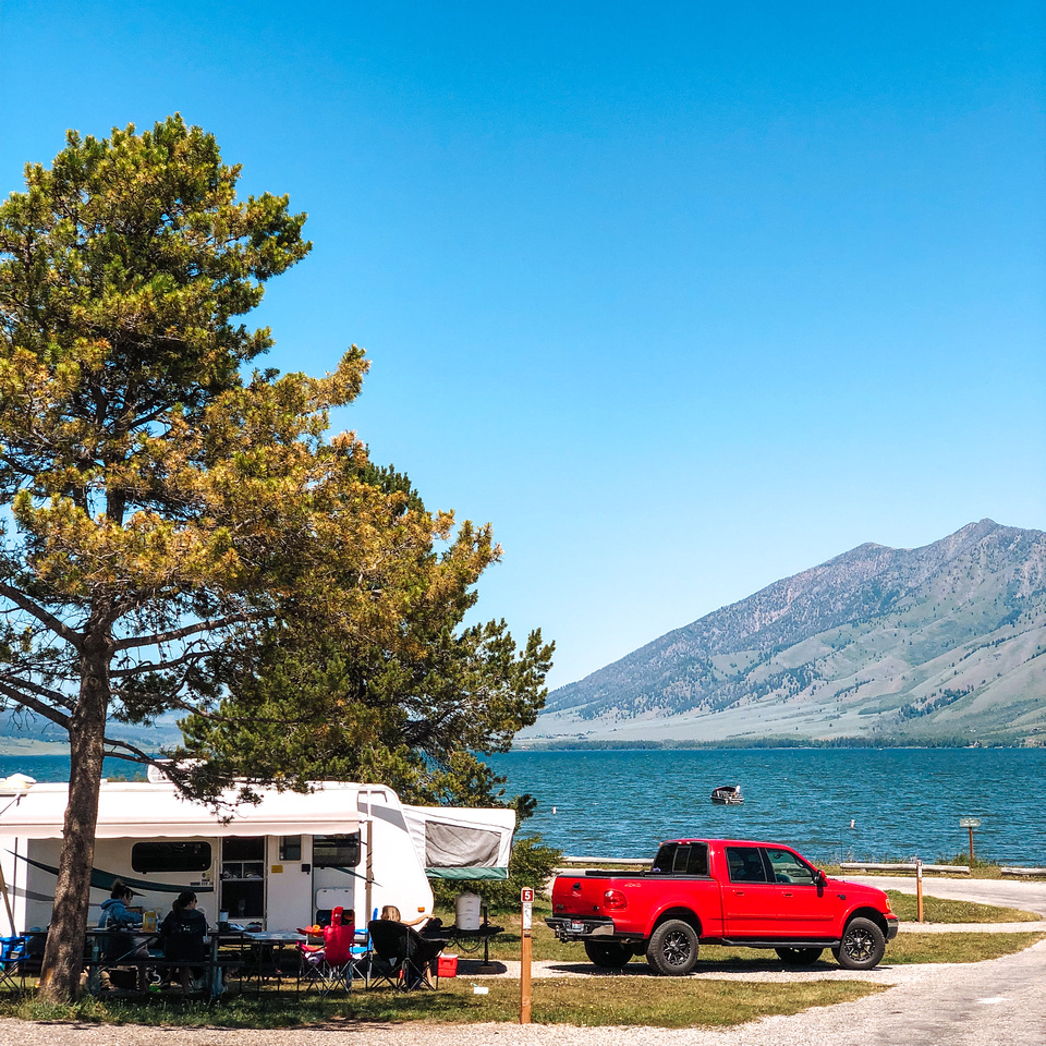 A view of a bright red Ford F-150 Lariat Supercab and a 2012 Starcraft Travel Trailer RV in front of Henrys Lake.  Idaho's Henrys Lake State Park sits just 15 miles from the West Entrance to Yellowstone National Park.  The Targhee National Forest and mountain range are visible in the distance.