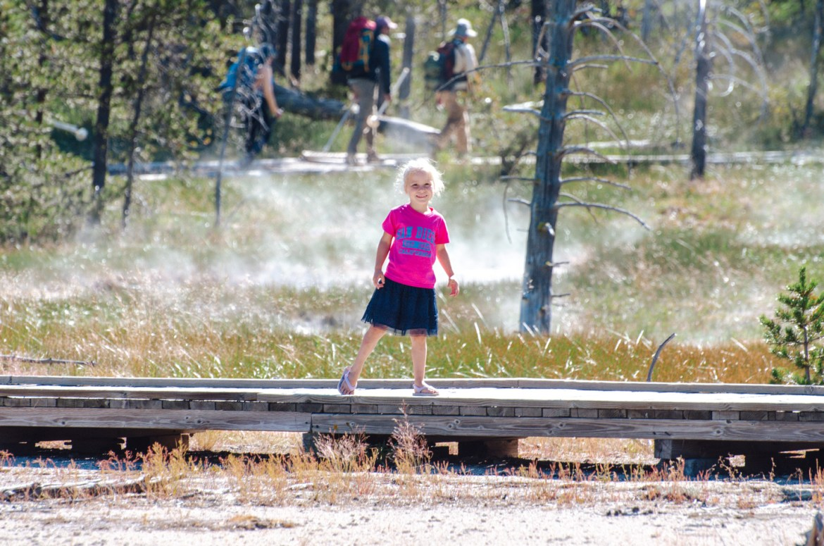 Yellowstone Hot Springs: A young girl smile as she stands on an elevated wooden walkway near volcanic thermal hot springs in Yellowstone National Park, Wyoming.