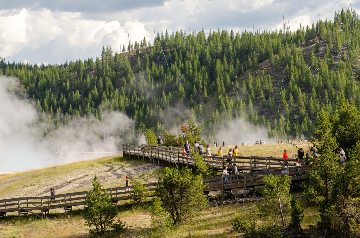 Yellowstone Vacation: Tourists walk up and down wooden walking paths at Grand Prismatic Spring in Yellowstone National Park, Wyoming.