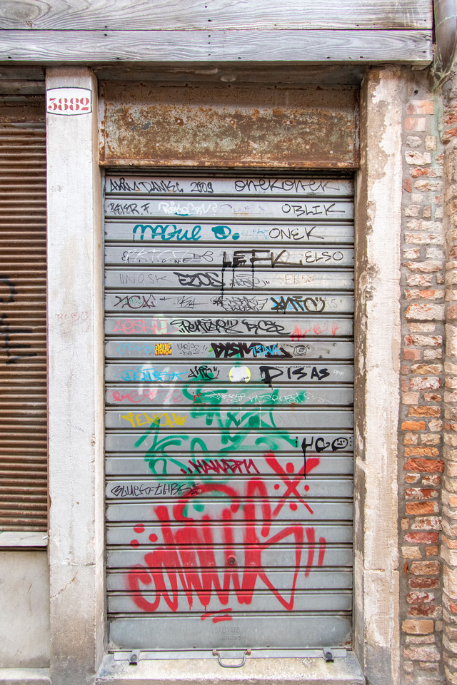 Close-up photo of hand-scrawled, painted graffiti on a door in Venice, Italy.