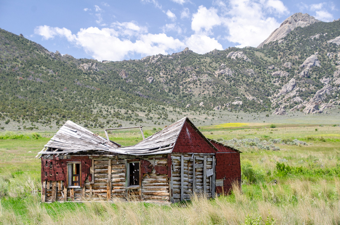 An old country cabin sits in a wide meadow in the high desert near the City of Rocks National Reserve.  The home's roof is collapsing.