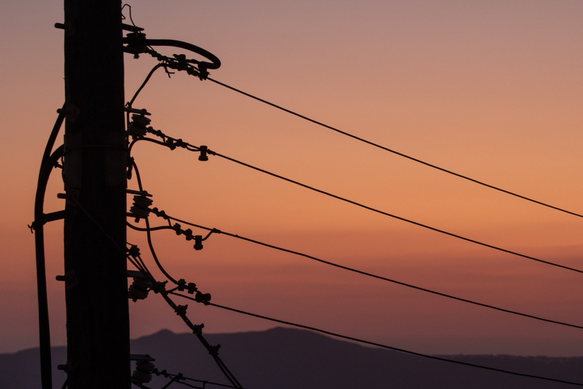 Free pics: A power pole and electric wires are silhouetted at sunset on the Greek Isle of Santorini.  The Caldera and Aegean Sea are visible beyond the utility pole.